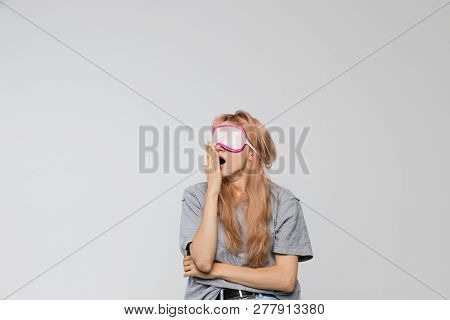 Studio Portrait Of Bored Teenager In Grey T-shirt Covering Mouth With Hand, Looking Left/drowsiness,