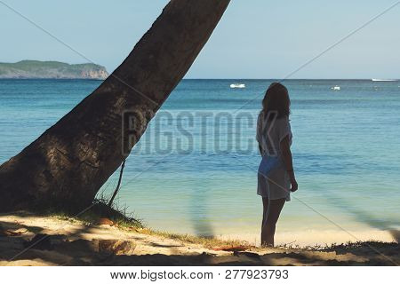 Beautiful Woman Standing Under Palm Tree On The Beach. Healthy People Lifestyle. Woman Relaxing On T