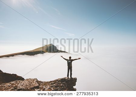 Happy Man Traveler Standing Alone On Cliff Edge Mountain Over Clouds Enjoying View Active Adventure