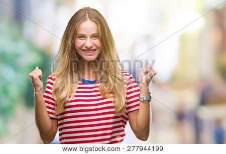 Young beautiful blonde woman over isolated background excited for success with arms raised celebrating victory smiling. Winner concept.