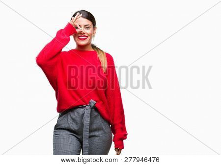 Young beautiful business woman wearing winter sweater over isolated background doing ok gesture with hand smiling, eye looking through fingers with happy face.