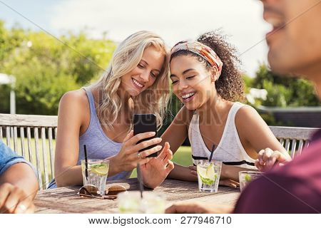 Two young women looking at smart phone and smiling sitting at table outdoor. Happy multiethnic girls taking selfie at outdoor cafeteria. Friends watching smartphone and laughing at park.