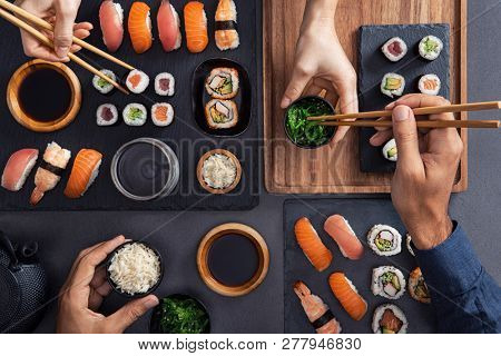 Top view of couple hands eating sushi food at japanese restaurant. High angle view of woman hand serving seaweed in to man. Couple eating and sharing sushi roll, maki, nigiri, uramaki.