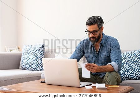 Mature man with spectacles and working on bills on laptop at home. Man with holding bills paying taxes with internet banking. Indian guy working on computer with invoice on table with copy space.