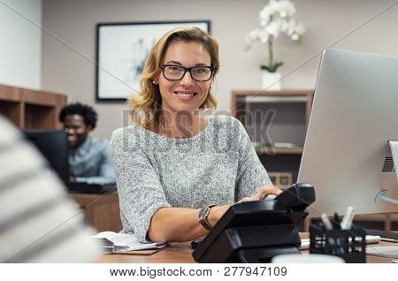 Mature beautiful woman at creative office and looking at camera. Portrait of receptionist working on computer in a coworking space. Successful businesswoman with eyeglasses sitting at help desk.
