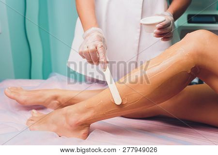 The Beautician Is Preparing For Depilation And Applying The Cream With Wax Stick On The Beautiful Fe