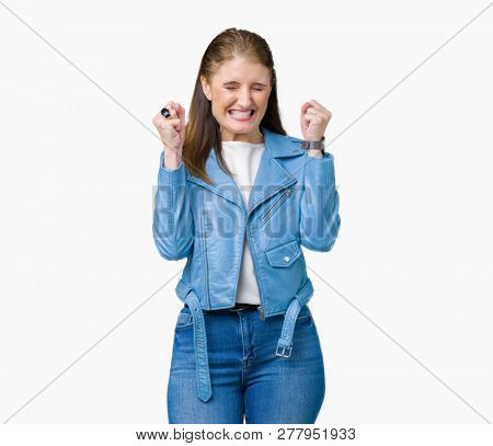 Beautiful middle age mature woman wearing fashion leather jacket over isolated background excited for success with arms raised celebrating victory smiling. Winner concept.