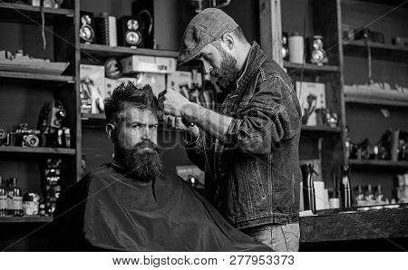 Hipster Client Getting Haircut. Barber With Hair Clipper Works On Hairstyle For Bearded Man Barbersh