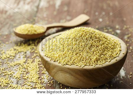 Raw Millet Groats In A Wooden Plate On A Shabby Wooden Background. Space For Text