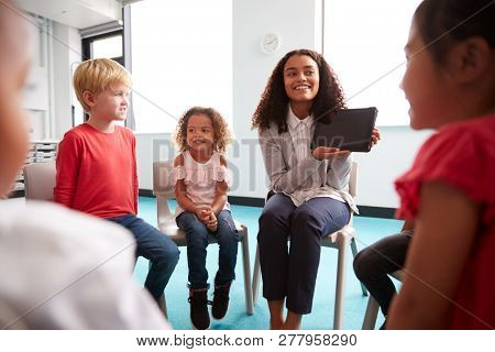 Over shoulder view of smiling young female school teacher showing a tablet computer to infant school children, sitting in a circle in the classroom, over shoulder view