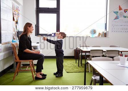 Schoolboy at primary school presenting a gift to his female teacher in a classroom, full length, side view