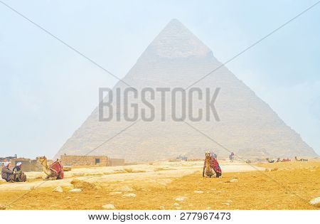Giza, Egypt - December 20, 2017:  The Old Cameleers Sit And Wait For A Clients, To Ride Around The G