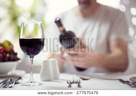 Man reading red wine bottle label in restaurant focus on glass