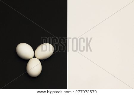 White Chicken Eggs On Black Part Of Contrasting Black And White Background. Minimalism Style.