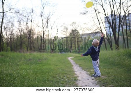 Child Boy Playing In The Park Throws A Flying Saucer