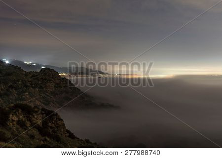 Foggy dawn view towards Porter Ranch in the west San Fernando Valley area of Los Angeles in Southern California.  Shot taken from hilltop in Santa Susana Mountains.