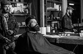 Hipster bearded client got hairstyle. Barber with hairdryer blows off hair out of cape. Barber with hairdryer works on hairstyle for bearded man, barbershop background. Barbershop concept poster