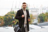 Photo of caucasian happy man 30s wearing jacket holding takeaway coffee while walking through city street poster