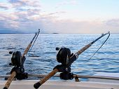 Two fishing rods held in fishing rod holders, attached to a back of a boat.  The rods are bent from the weight of the down riggers.  People are trolling for salmon of the coast of British Columbia. poster