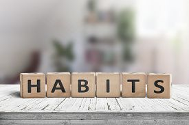 What Is Your Habits? Sign With The Word Habits On A Wooden Desk In A Bright Room