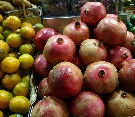 Many Pomegranates And Tangerines On The Table