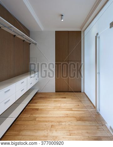 Empty Wooden Wardrobe Closet With Shelves And Drawers In Dressing Room. Vertical View Of Modern Hous