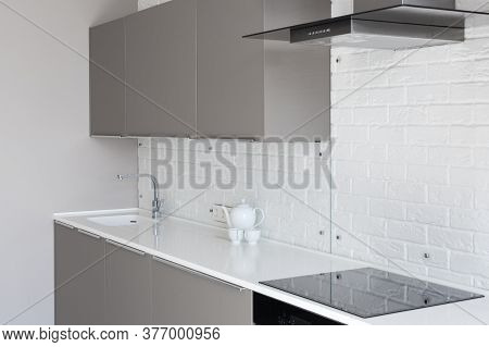 Side View Of Modern House With Contemporary Interior Design In Kitchen, Cabinet Furniture, Teapot An