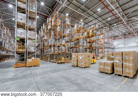 Large Industrial Warehouse. Many Cardboard Boxes Stand On A Loading Dock.