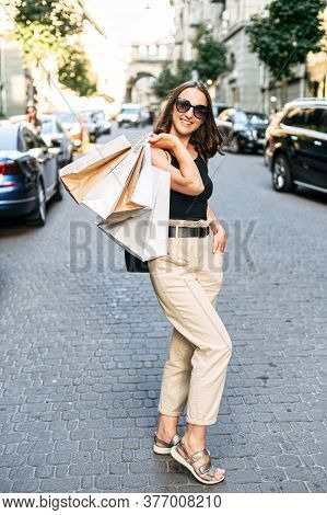 Charming Young Woman Has A Shopping Day In The City, She Stands On The Street With Shopping Bags Thr