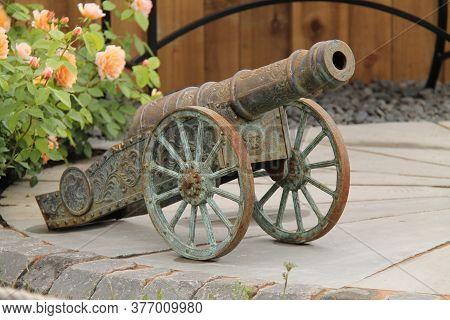 A Rusty Ornamental Cannon As A Garden Display.