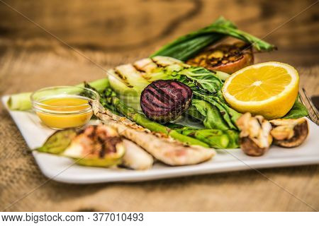Grilled Fish Fillet With Fresh Vegetables Served On Plate. The Food In The Restaurant. Food Styling