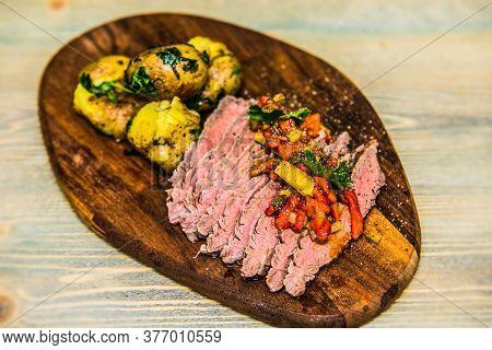 Grilled Meat Slices And Potatoes With Fresh Vegetables Served On Wood Plate. The Food In The Restaur