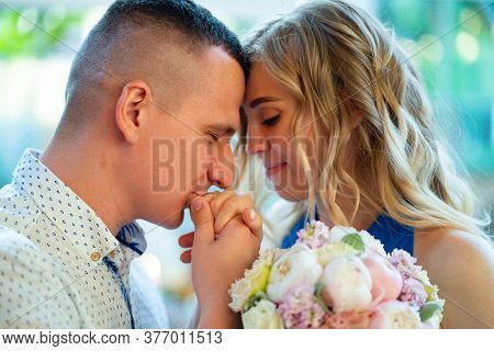 The Groom Kisses The Bride Hand With Wedding Ring. Proposal To Marry Him.