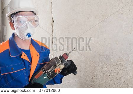 A Worker In Safety Glasses, A Helmet And A Mask Drills A Wall With A Jackhammer, Looks Into The Came