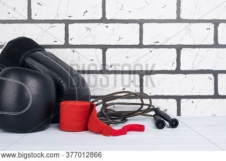 Black Gloves With Jumpers And Protective Red Bandages On The Gym Floor