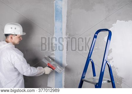 A Repairman In A White Helmet Applies The Mortar With A Spatula To The Mesh Glued To The Seam On The