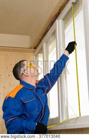 A Man In Construction Clothing Measures A Window Opening And Looks At The Results