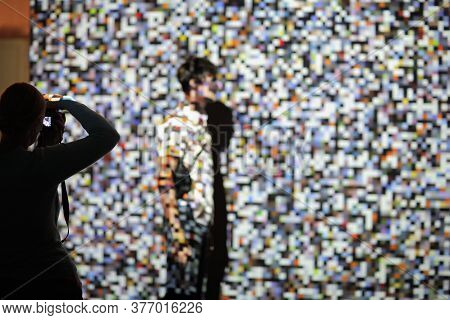 The Man On The Background Of The Projection Of Colored Pixels. Pixels Are Chaotic In Shape And Color