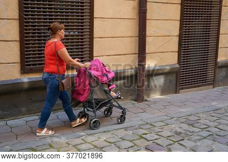 Woman Pushes A Stroller, In The Old Town Mom Pushes A Stroller With A Sleeping Baby
