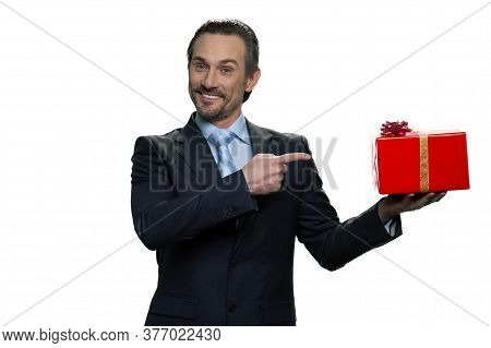 Generous Formal-dressed Man Pointing At The Gift. Smiling Middle-aged Male Isolated On White Backgro