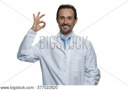 Cheerful Doctor Showing Okay Gesture. Middle-aged Practitioner Isolated On White Background.