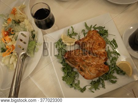 Florentine Steak With Arugula, Lemon, Glass Of Red Wine And Vegetable Salad