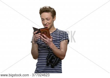 Teenage Boy Is Reading Something In His Passport. Happy Young Teenage Travaler Is Looking At His Pas