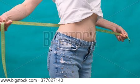 Woman Measuring Her Waistline. Perfect Slim Body. You Can Get The Same Results. Close-up Of A Woman
