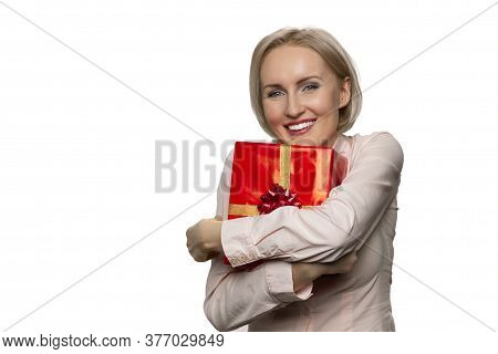 Portrait Of Smiling Woman Holding In Hands Hugging Celebratory Gift Box. Giftbox With Gold Ribbon.