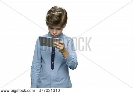 Focused Little Boy Enthusiastically Watching A Movie On His Smartphone. Holding Phone On One Hand In
