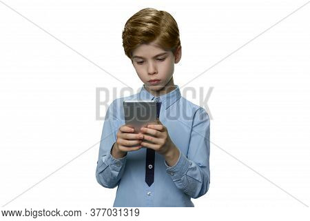 Boy In Blue T-shirt Enthusiastically Looking At His Smartphone. Teenager Holding Mobile Phone With B