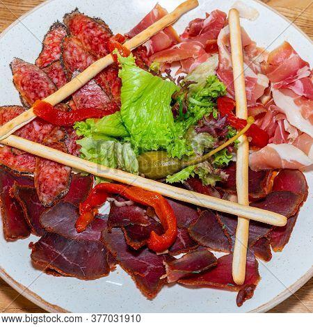 Plate With Delicacies. Trio Of Dried Delicacies. Basturma, Prosciutto, Sausage Flat. White Plate. Wo