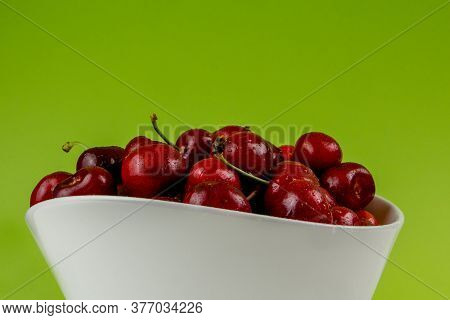Collection Of Many Cherries In White Ceramic Bowls On Green Background Isolated