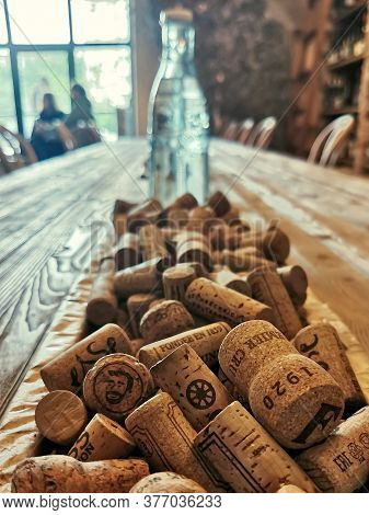 Moscow / Russia - 07.18.2020: Close-up Of Wine Corks On A Wooden Table And A Glass Bottle In The Bac